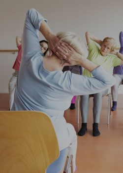 senior women exercising yoga and pilates sitting on chairs, following the instruction of their teacer